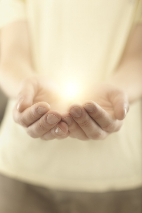 Male hands holding rays of glowing light.
