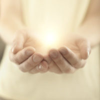 Male hands holding rays of glowing light. Magic energy in hands. Soft focus